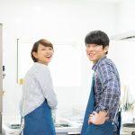 笑顔で後ろを振り向くキッチンに立っている男女2人